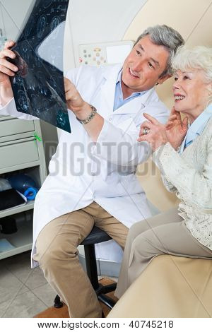 Mature male radiologist explaining CT scan x-ray to senior female patient