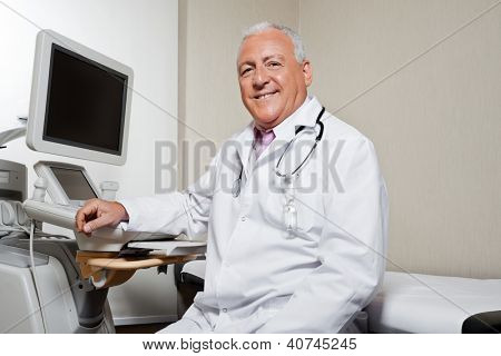 Portrait of senior male radiologist sitting by ultrasound machine at clinic