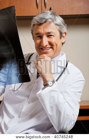 Portrait of happy mature male radiologist with x-ray sitting at clinic