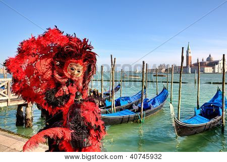 VENICE - MARCH 04: Participant in red costume and mask standing near gondolas on Grand Canal against San Giorgio Maggiore church during traditional carnival in Venice, Italy on March 04, 2011.