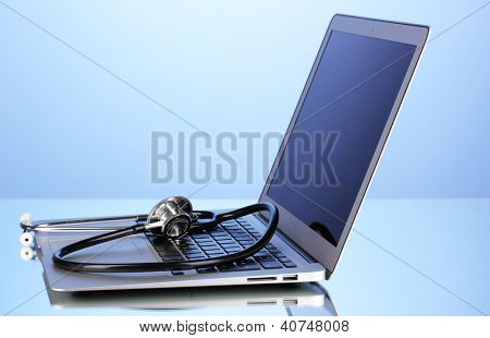 Silver notebook with a stethoscope on blue background with reflection