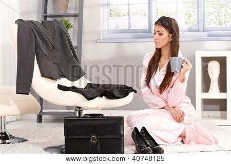 Sleepy businesswoman getting ready for work in morning, sitting in pyjama in living room having coffee.