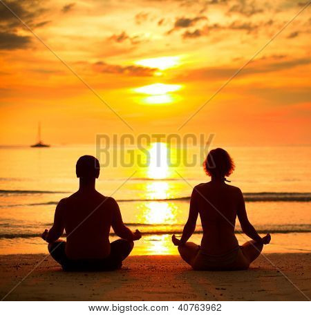 A young couple sitting on the beach of the sea in the lotus position at sunset, yoga practice.