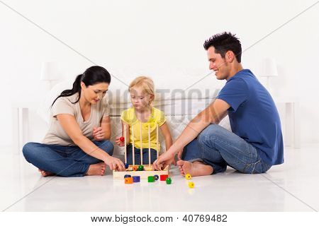happy family playing toy game with daughter on bedroom floor