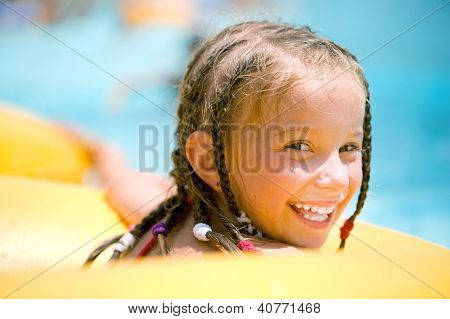Smilyng little girl  sitting on inflatable ring in swimming pool.