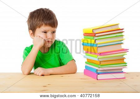 Pensive boy with stack of books