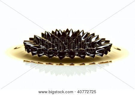 Macro of Ferrofluid structure induced by a neodymium magnet in golden light. Ferrofluid is a colloidal liquid of nanoscale particles in a carrier fluid that becomes magnetized by approaching a magnet.