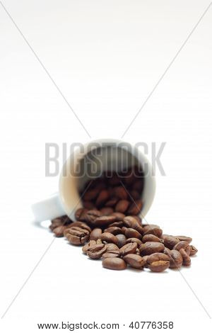 Espresso beans with a small cup