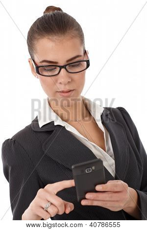 Attractive young businesswoman using smartphone, isolated on white.