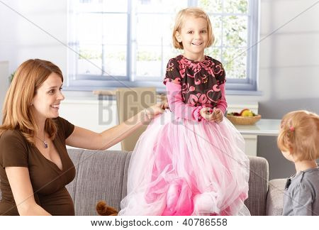 Happy little girl trying on princess outfit with pregnant mother and little sister.