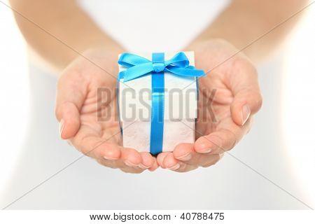 Dekorative Geschenkbox mit einem Türkis Band gebunden und Bogen sorgfältig schalenförmig in Frauenhänden als sie giv