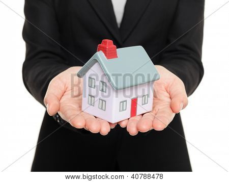 Real estate agent showing mini house / home closeup of female realtor hands showing miniature model house isolated on white background.