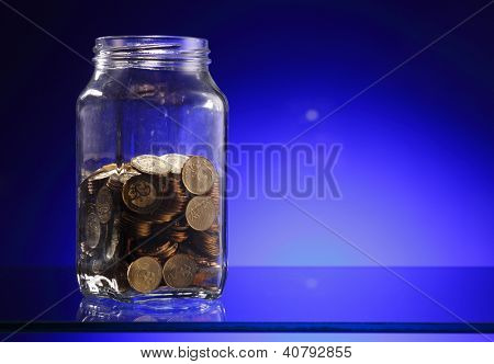 Glod coins in jar on the blue background