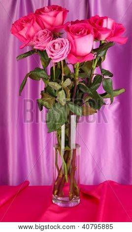 Beautiful pink roses in vase on purple fabric background