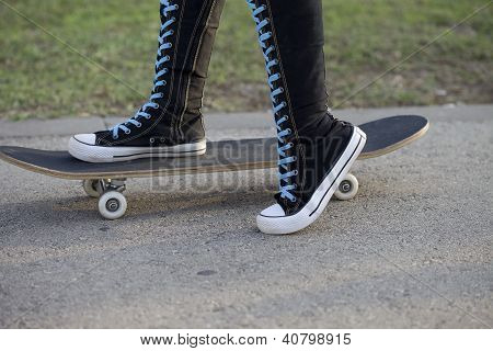 Female with skateboard in high knee sneakers.