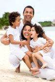 stock photo of family vacations  - happy family smling at the beach while on vacation - JPG