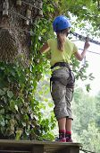 picture of parkour  - Teenage girl is standing on the platform high up on the tree - JPG