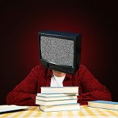stock photo of brainwashing  - Young adult bold student with TV head and few books sitting at the table - JPG