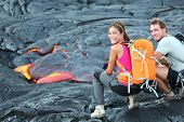 Hawaii lava tourist on hike. Tourists hiking near flowing lava from Kilauea volcano around Hawaii vo