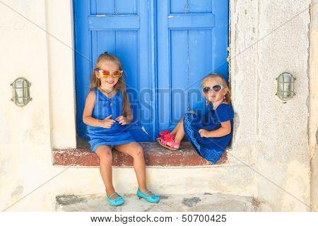 Little Cute Sisters Sitting Near Old Blue Door In Greek Village Of Emporio, Santorini