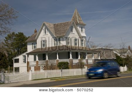 Blue Van Passing Victorian House