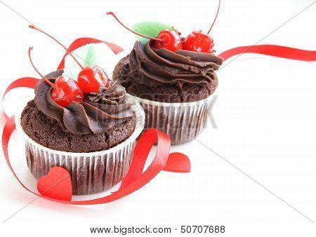 festive (birthday, valentines day) cupcake decorated with chocolate ganache and cherries