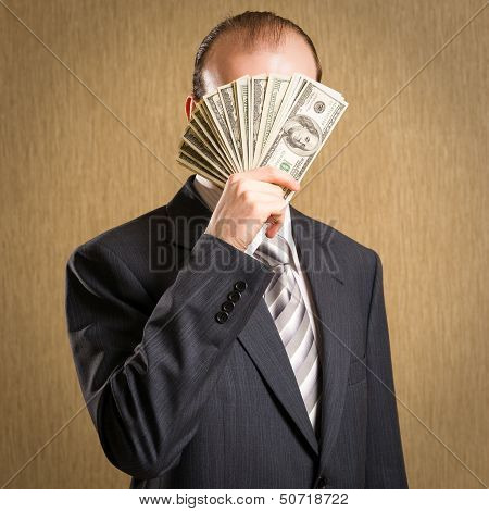 Man Concealing His Face With A Fistful Of Money