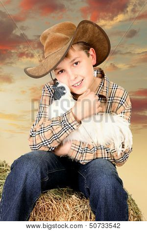Farm Boy Sitting On Bale Of Hay Holding A Chicken