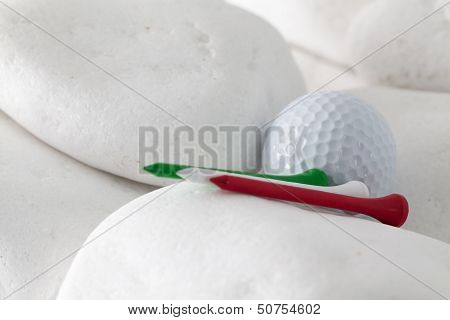 Golf Ball And Tees Between White Stones