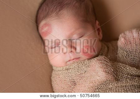 Newborn Baby With Lipstick Kisses On Face