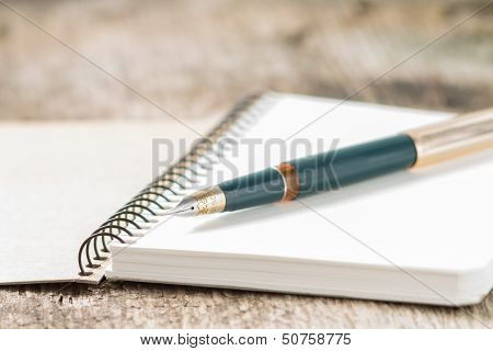 Closeup Photo Of Notebook With Old Golden Ink Pen At Wood Background