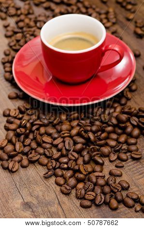 Arabica Coffee Beans And Red Mut On A Black Brown Wooden Table