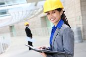 picture of asian woman  - A pretty asian woman working as architect on a construction site - JPG