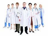 stock photo of male female  - happy team of successful doctors standing together in hospital gowns - JPG