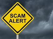 picture of precaution  - A road warning sign against a stormy sky with words Scam Alert Warning of Scam - JPG