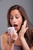 stock photo of shock awe  - Young girl receiving shocking and unexpected news over the phone - JPG