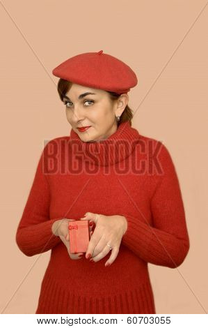 Woman in red with beret holding a gift