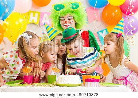 Children With Clown Celebrating Birthday Party And Blowing Candle On Cake