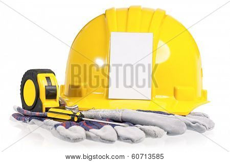 Yellow hard hat with work gloves and tools including screwdriver and a tape measure on a white background