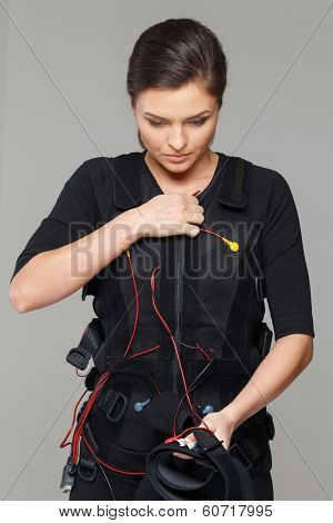 Young woman putting on  Electro Muscular Stimulation EMS exercise training costume