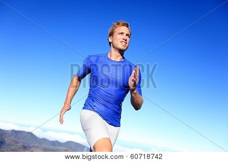 Athlete runner sprinting running to success. Fit male fitness sprinter training in sprint with determination and strength. Handsome athletic man working out outside on blue sky.