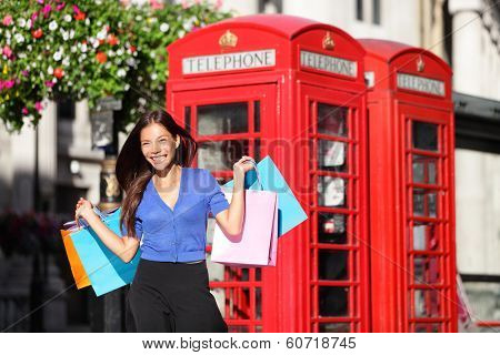 England London shopping woman shopper holding shopping bags by red phone booth. Female shopper smiling in London, England, United Kingdom during spring or summer. Mixed race Asian Caucasian model.