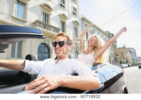 Car people - man driving with happy woman. Male driver wearing sunglasses. Young couple having fun in car driving on travel vacation together. Lifestyle with beautiful cheerful lovers.