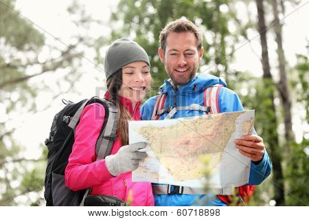 Hiking couple looking at map hiking in forest. Young interracial hiker couple, Asian woman, Caucasian man. Hikers outside wearing jackets.