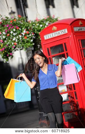 London shopper girl happy excited holding shopping bags by red phone booth. Woman shopping smiling in London, England, United Kingdom during spring or summer. Mixed race Asian Caucasian model.