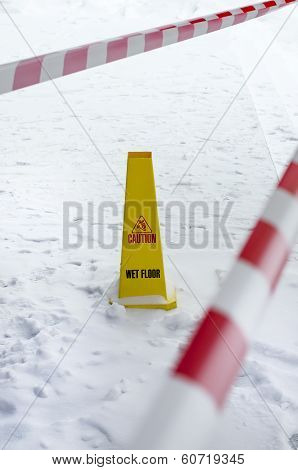 Yellow plastic wet floor sign on snowed floor.