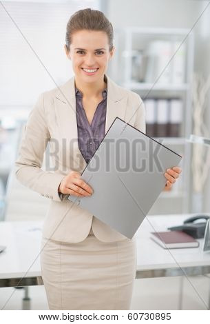 Portrait Of Happy Business Woman Standing With Folder In Office