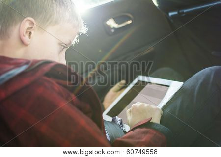 Boy in car playing on tablet pc