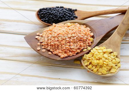 different kinds of lentils - red, yellow and black in wooden spoons