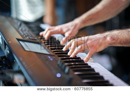 Closeup shot of male hands playing the piano.